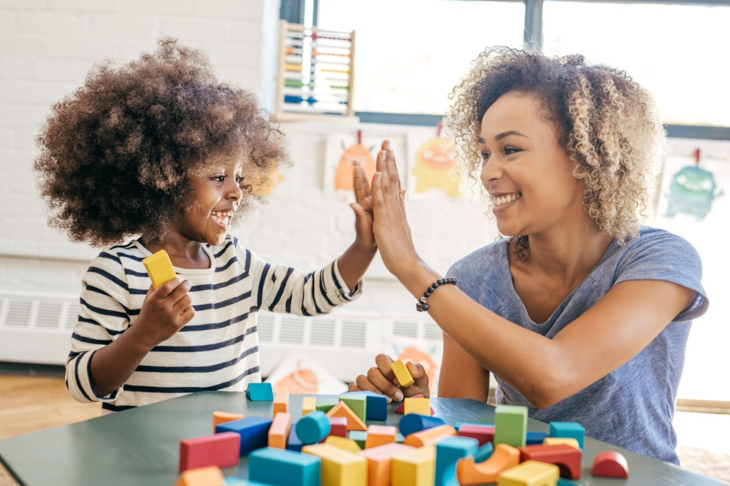 Teacher and young girl high-five while sitting next to each other