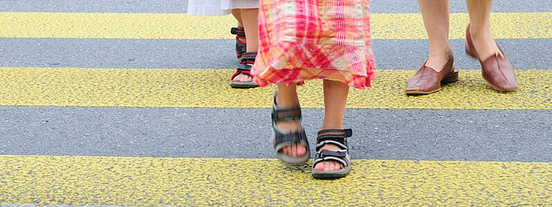 A pre-K student walks to school with her mother.