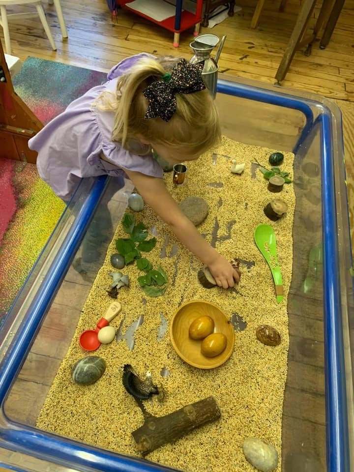 Sensory table filled with rice and toys